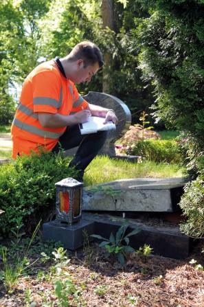 Maximilian Vages bei der Arbeit: Diesen Grabstein musste er vorsichtshalber niederlegen, da Unfallgefahr bestand. Der Anschluss an die Bodenplatte war nicht in Ordnung. (Foto: ©Isabella Raupold)