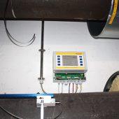 """Der Ultraschallsensor im Vordergrund ist einfach auf das Fernwärmerohr geschnallt. Die Auswertung der Signale erfolgt im Messwandler """"Clamp-On Ultraschall-Station"""". Die Station überträgt die definierten Werte dann auch an die GLT. (Foto: WDV-Molliné)"""