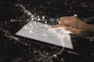TRILUX Smart City 300x200 - double exposure hand using tablet and city on night background