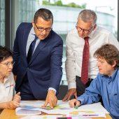 """""""Geschäftsführer Frank Molliné (stehend links): """"Fairness ist die beste Kundenbindung. Mehr Energieeffizienz in Gebäuden setzt individuelle Messstellenkonzepte und offene Systeme voraus. Das bedeutet eine Abkehr von einem Geschäftsmodell, das heute noch weit verbreitet ist, dem Verkauf von proprietären Messgeräten."""""""