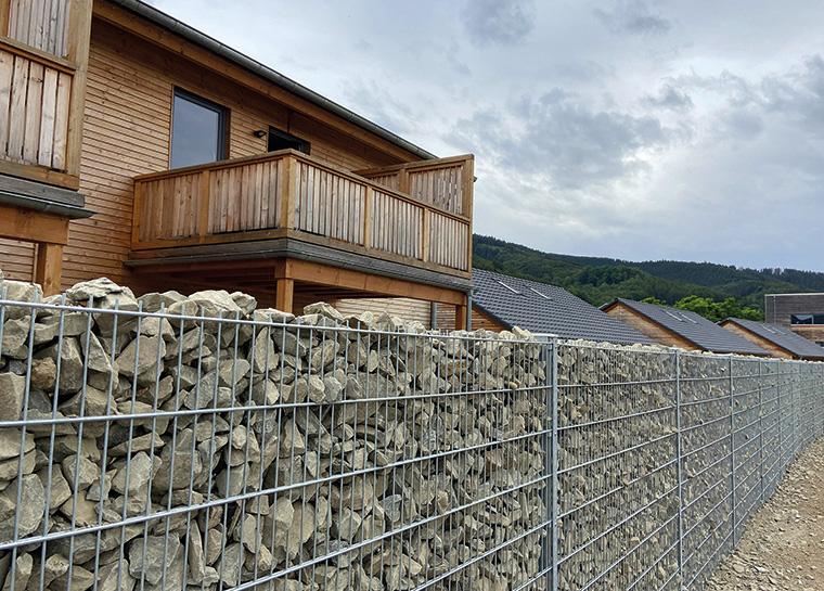 Eine Steinmauer mit 75 m Länge trennt die Ferienhausanlage vom Jugendcamp und den Wohnmobilstellplätzen.