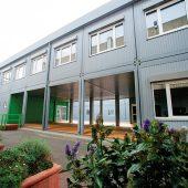 Die modularen Schulgebäude von Algeco verfügen über große überdachte Eingangsbereiche und rollstuhlgerechte Zugänge. Zudem lassen die großen Fenster viel Tageslicht in die Klassenräume.