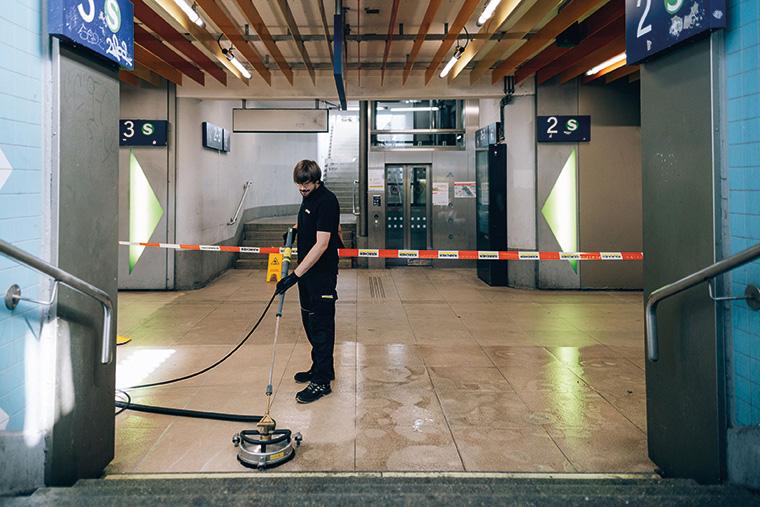 Sebastian Nann, Projektleiter, reinigt mit einem an einen Heißwasser-Hochdruck-Trailer angeschlossenen Flächenreiniger die Natursteinplatten in der Bahnhofsunterführung.