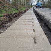 Dieses WALLSTOP Rüttelbankett entlang der Landstraße im Saarland weist eine Breite von 50 cm, eine Stärke von ca. 30 cm und eine Querneigung von ca. 3% auf. Nach der Fertigstellung des Banketts wurde die Asphaltfahrbahn saniert und daran angebaut.