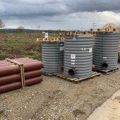 Bereit für den Einbau im Ortsteil Allmannsweier: Die Funke Kunststoffschächte DN 1000 mit dem Auftrieb entgegenwirkendem Profilrohr und die HS®-Kanalrohre DN/OD 250 für den Schmutzwassersammler. (Foto: Funke Kunststoffe)